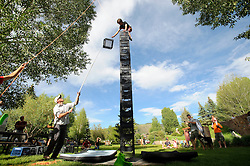 In a competition of balance and agility, Jacob Lorenz, 13, teters atop 17 milk crates he stacks with the help of Micah Rush during the opening ceremonies for the Jackson Hole Mountain Games on Friday at Phil Baux Park.