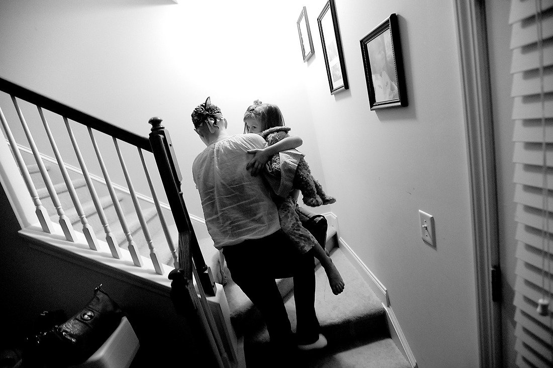 Exhausted after a long day, Keri carries her daughter, Kassidy, upstairs to get ready for bed. — © /
