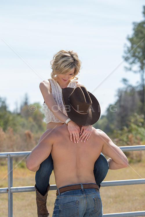 shirtless cowboy enjoying time with a girl sitting on a fence in rural America