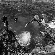 Divers along the Malecon in Havana.