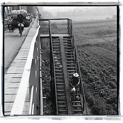 A man goes down a bunch of stairs with his bicycle. He reachs the island located between two arms of the river. On the bridge, a woman carries two huge bags, riding a bicycle.