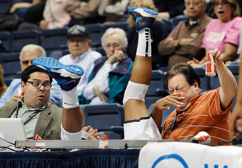 Connecticut's Kaleena Mosqueda-Lewis, center, chases a ball out of bounds, falling between Hartford Courant writer John Altavilla, left, and Associated Press freelancer Ken Davis, right, during the second half of an NCAA college exhibition basketball game in Storrs, Conn. (AP Photo/Jessica Hill)