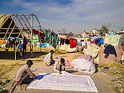 04 MARCH 2017 - KATHMANDU, NEPAL: Men make comforters filled with kapok in an IDP camp in the center of Kathmandu. The men do not live in the camp, but they try to sell the comforters to camp residents. The camp opened days after the April 2015 earthquake devastated Nepal, killing almost 9,000 people. At its peak, about 1,800 families lived in the camp. The camp is still open nearly two years after the earthquake, about 400 families currently live in the camp. Camp residents say the Kathmandu municipal government is trying to close the camp and is encouraging residents to find new housing. They said the government is cutting off services to the camp and last week stopped the free distribution of water, although water can be purchased for delivery. Most of the people in the camp came to Kathmandu from rural villages in the mountains in the weeks after the earthquake. Many of the residents of the camp, technically homeless, have found work in Kathmandu's bustling construction industry, rebuilding homes destroyed in the earthquake.       PHOTO BY JACK KURTZ