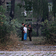 Two North Korean soldiers check a North Korean young person in the bank of the Yalu river in Sinuiju
