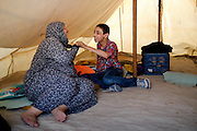 Grandmother playing with her dissabled grandson. <br /> Refugee camp Kara Tepe near Mytilene city. It hosts Syrian refugees who are waiting for their registration papers that will allow them to stay in Greece for some time till they can move to an other European country.