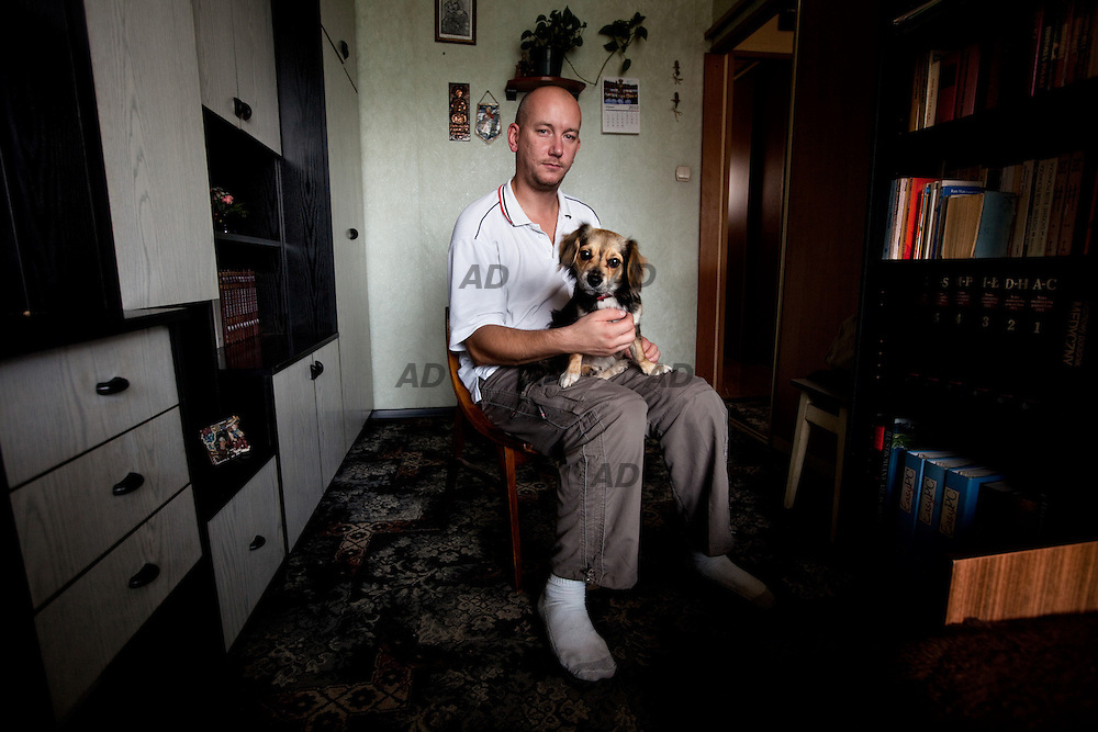 """Mariusz, 30 years old, and his dog Pearl. He has been working for Fiat in Tychy for about three and a half years. """"I'm the welding line operator... just a normal worker. Sometimes it's good and sometimes it's not so good, but one can't complain... or at least in my opinion. I don't know what other people think. Let's see what happens next, hopefully everything will go well."""""""