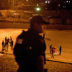 A Mexican Federal Police officer looks on as U.S. Border Patrol investigate the U.S. side of the scene of the shooting of a 15 year-old boy, who was killed by a U.S. Border Patrol agent in Ciudad Juarez, Chihuahua on June 7, 2010 after he had tried to cross.
