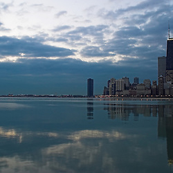Just before sunrise, the clouds depart from the Chicago skyline to reveal the Hancock Building reflecting in the waters of Lake Michigan. This picture was taken from the pier at the North Ave. Beach.
