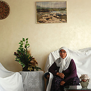 Tevrat and her husband Yusuf grew up living as nomads, but Yusuf is now a wealthy livestock merchant in Gaziantep. They decorate their apartment with plastic plants and photos of their former life.