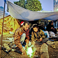 A father and son start a fire beside their tent in Tahrir Square in Cairo, Egypt. February 2011.