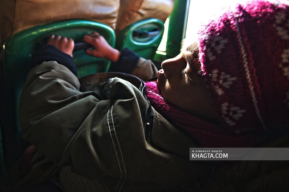 A small kid holding sleeping in a bus to Rekong Peo, Kinnaur, Himachal Pradesh