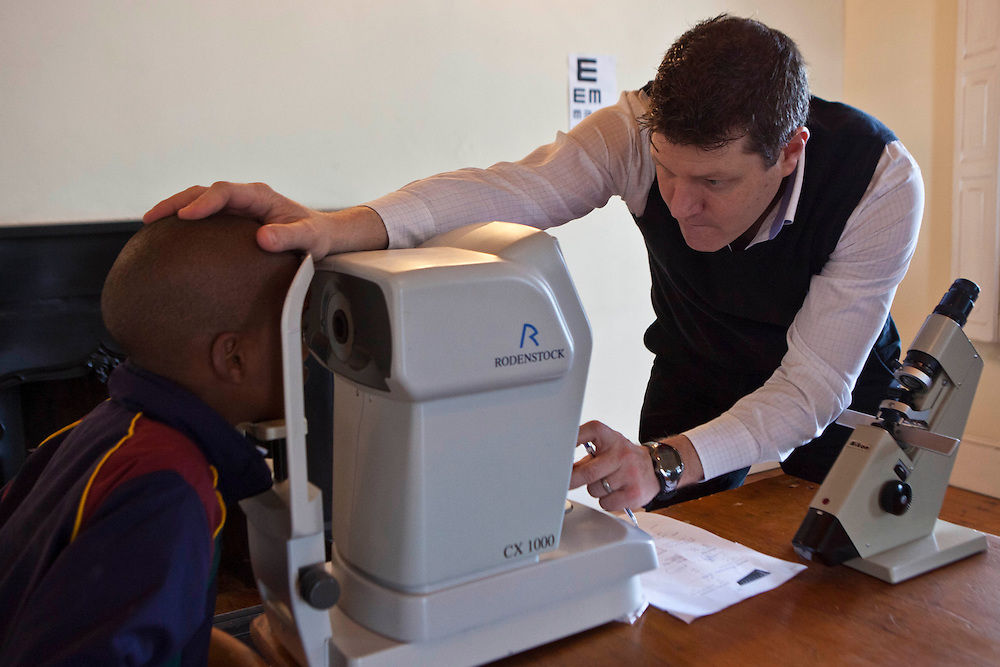 A male optician performs an eye test on a young African school boy in a classroom in Zonnebloem School, Cape Town, South Africa.  He is using a diagnostic portable Rodenstock keratometer (opthalmometer) machine which is an auto refractor and measures the curvature of the cornea.  The eye test is being provided by Mullers Opticians who volunteer their staff to visit schools and perform eye tests on all children in school grade 2.