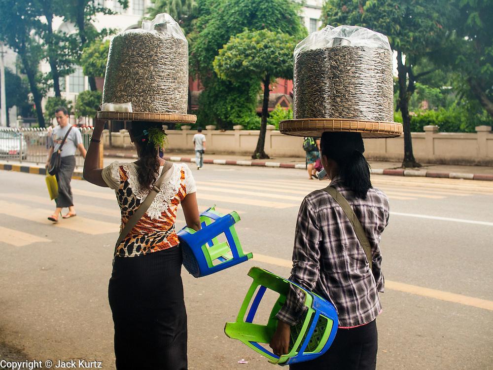 10 JUNE 2014 - YANGON, MYANMAR:   Women who sell watermelon seeds as a snack walk down a street in Yangon, Myanmar.   PHOTO BY JACK KURTZ