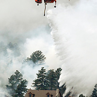 A helicopter tanker drops water behind a house in Colorado's High Park Fire, about 15 miles northwest of Fort Collins June 11, 2012.  The fire was estimated to be at 37,000 acres according to the county sheriff June 11, 2012. REUTERS/Rick Wilking  (UNITED STATES)