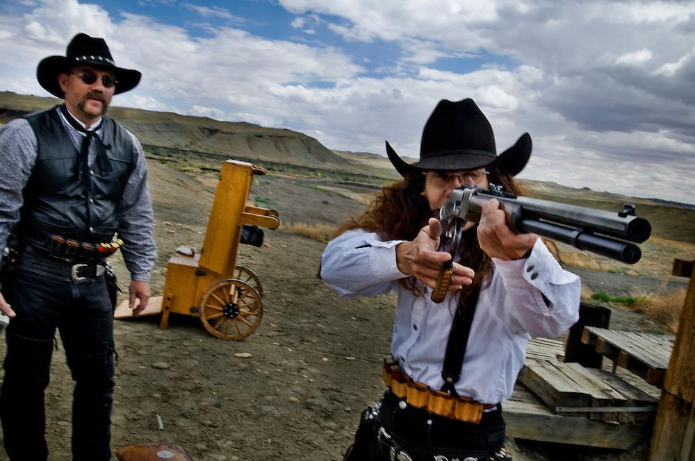 "Greyhound trip..Robert ""Doc"" Nelson and his wife Kaye Nelson aka ""Senorita Tira Todo"" practicing cowboy action shooting on a shooting range in Green River, Utah..Photographer: Chris Maluszynski /MOMENT"