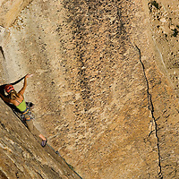 Mikey Schaefer, belayed by Kate Rutherford, does the first free ascent of Thin Red Line on Liberty Bell...Route Info:.Thin Red Line (5.9 C2 or 5.12 C).On Liberty Bell, Washington Pass, Washington. El 7,720'..FA July 29, 1967 by Jim Madsen and Kim Schmitz at Grade V 5.9 A3.FFA September 15, 2008, Kate Rutherford and Mikey Schaefer at 5.12c..One bolt was replaced on the original route. A new variation was added to skirt the pendulum pitch; X# of bolts placed on this pitch. Several pitons were fixed to increase safety for free climbers; Mikey requests aid climbers leave these in place so free climbers can simply walk up to the route and safely climb it. However, he acknowledges it will be up to the traditionalists to decide if they can tolerate safe free climbing on a classic aid line.