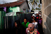 Dominican Republic: Musicians and locals of the Bateys (plantations) file through an alleyway ahead of the start of the GaGá  procession of El GaGá de San Luis on the outskirts of Santo Domingo...