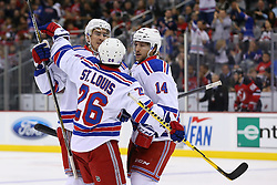 Oct 21, 2014; Newark, NJ, USA; New York Rangers left wing Chris Kreider (20), New York Rangers right wing Martin St. Louis (26) and New York Rangers right wing Chris Mueller (14) celebrate Kreider's goal during the first period of their game against the New Jersey Devils at Prudential Center.