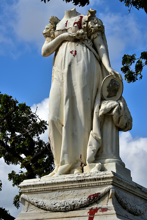 Statue of Beheaded Empress Jos&eacute;phine in Fort-de-France, Martinique <br /> Marie Jos&egrave;phe Rose Tascher de La Pagerie was born in Martinique in 1763 and, after her husband was guillotined, she became the wife of Napol&eacute;on Bonaparte and the Empress of the French.  In her honor, this statue was erected in 1859 at the La Savane Park. Notice she is holding a rose, the name she preferred as a girl while living on a nearby sugar plantation.  Also notice she is headless. This vandalism occurred in 1991 because of a bitter resentment for her encouraging the reinstatement of slavery in 1802. The red paint &ldquo;blood&rdquo; stains were added later.