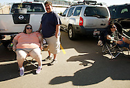 """Jolene Alirez (L) and husband Tom wait in line for an open casting session for season 11 of """"The Biggest Loser"""" television show studies the application for the show in Broomfield, Colorado July 17, 2010. Over 600 people, many spending the night on the sidewalk outside the hall applied for a chance to be on the show and win $250,000.  REUTERS/Rick Wilking (UNITED STATES)"""