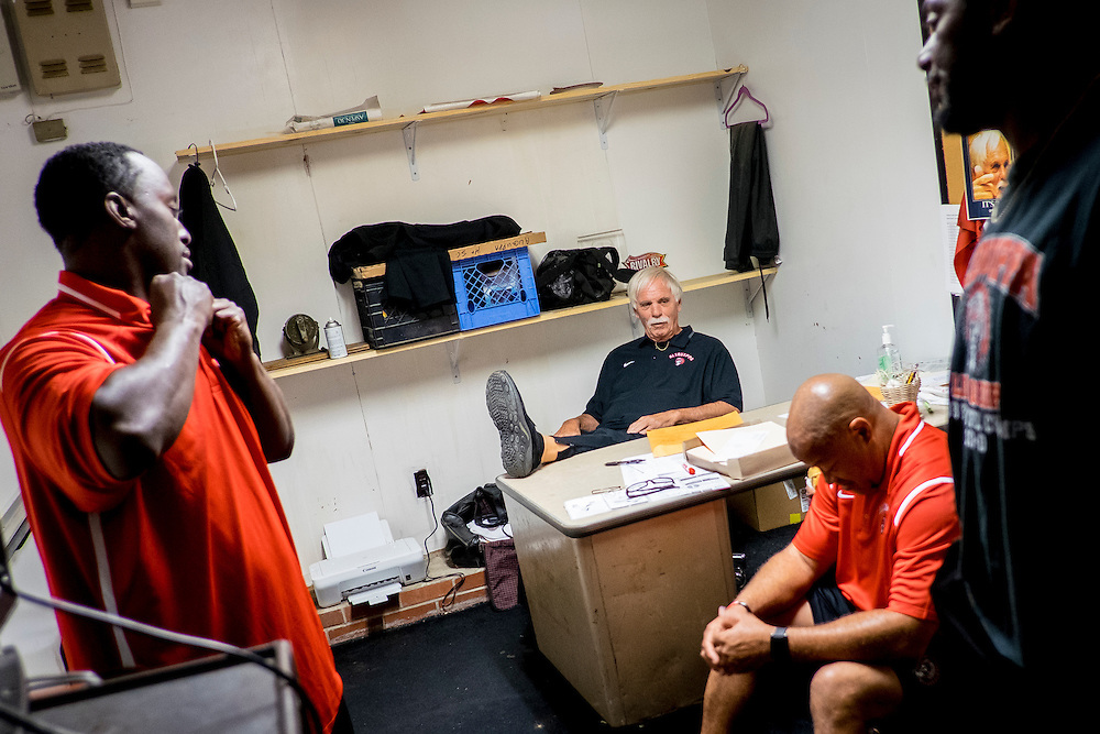 Aliquippa head coach Mike Zmijanac meets with his coaching staff before their homecoming game.<br /> <br /> Zmijanac has never played a down of organized football but he is the winningest coach of what is said to be the best high school program in the region. <br /> <br /> Due to the obstacles of violence and drugs in Aliquippa, Zmijanac says that he loses six or so of his players to the pull of the street each year. And although he will not hesitate to suspend a star player, he maintains an open-door policy if they want to come back, believing that everyone deserves a second chance and that he can't give up on them.<br /> <br /> The school has one of the smallest enrollments in the Western Pennsylvania Interscholastic Athletic League (WPIAL) with the class of 2013 having only 58 kids, including 28 boys.<br /> <br /> Technically, they could play against Class A completion but they elect to play at the AA level.<br /> <br /> Pretty steep obstacles for a coach and team to overcome, but the team averaged 10 wins a year for the past 30 years. Last year Aliquippa played in its 25th WPIAL championship game, the most of any school in the district and they have won a record 15 titles. 2014 was the seventh year in a row that the Quips were in the final, also a record.<br /> <br /> The team was the training ground to NFL greats like Mike Ditka, Sean Gilbert, and Ty Law, all of whom were Aliquippa graduates.