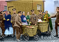 British troops pose for the camera after buying fruit from some enterprising street vendors prior to embarking on troop ships in Dublin. One of the vendors seem to be resisting the charms of the Tommy on the far left. This image has been digitally edited to add colour to its original black and white format.  (Part of the Independent Newspapers Ireland/NLI Collection)