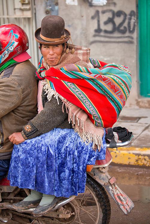 South America, Peru,Juliaca, native woman riding on bike