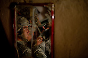 Specialist William White of the 82nd Airborne, 1/508, Alpha Company, Third Platoon is reflected in a mirror broken during their search for weapons in a home in Sangin, Helmand province, Afghanistan on Friday, April 6. 2007.