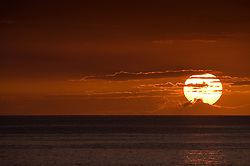A giant sun at sunset as seen from the Keauhou Beach Resort next to Kahaluu Beach Park in Keauhou on the Big Island of Hawaii.