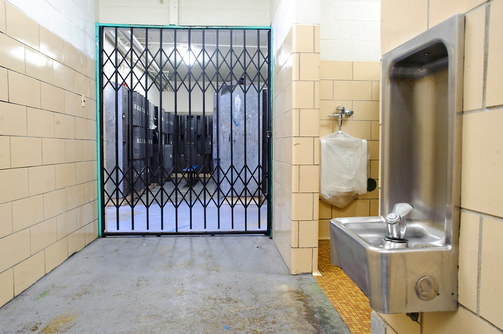 (photo by Matt Roth).Friday, May 14, 2010..The boy's locker room at the Baltimore Freedom Academy is in such dangerous disrepair, students are not allowed to use it. Water is a serious issue at the fifty-year-old school building. Aside from a wrapped up urinal, the fountains are turned off across the school due to high lead levels in the water due to antiquated pipes. Asbestos makes fixing the pipes hazardous...The building housing the Baltimore Freedom Academy, a grade 6-12 Baltimore public charter school focusing in social justice, was built in 1960. Fifty years later, the school is in disrepair. Old pipes make water from the fountains undrinkable. Asbestos makes repairing/replacing the pipes a hazard. The school has no air conditioning which makes the year-round school unbearable in the summer. The most derelict area is the boys locker room, where students are not allowed.