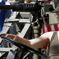 A woman sits in a jeep equipped with a  .50 cal. machine gun during the Knob Creek Machine Gun Shoot near West Point, Kentucky April 10, 2005. Thousands of machine gun and military hardware enthusiasts attended the event held each year over weekends in the spring and fall.