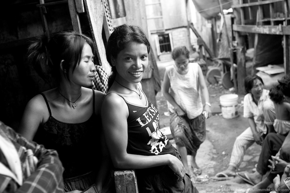 "Prostitutes Srey Dah, left, and Srey Bee, right,  relaxing before a night of work while at home in the slum where the non governmental organization ""Acting for Women in Distressing Situations"" (AFESIP), conducts outreach and provides services in Phnom Penh, Cambodia. The permanent structure, a decaying four story building known simply as 'The Building', was built in the 1960's as transitional housing and now hosts a shantytown where many of the city's poor live, including many prostitutes, and is believed to have the highest rate of HIV infection in the city. AFESIP hands out free condoms, instructs prostitutes on HIV prevention, and conducts outreach in case the prostitutes need medical services, choose to leave their profession, or can report on cases of sex trafficking. AFESIP offers housing, education, training, and counseling for women who are victims of sex trafficking, worked as prostitutes, or are escaping domestic violence. Founded by Somaly Mam, who herself was once a prostitute and victim of trafficking and domestic abuse, AFESIP has three facilities in Cambodia and works with other NGO's to provide long term care for the women."