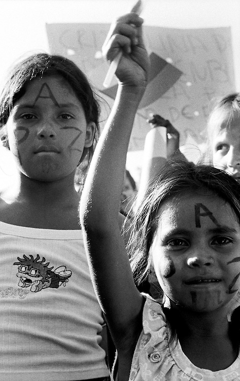 Young girls with PAZ (peace in Spanish) painted on their faces wave flags during a peace march by locals at a FARC camp. Los Posos, Caqueta.<br />