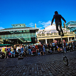 Unicyclist and juggler entertaining the crowd, Covent Gardens, London, England