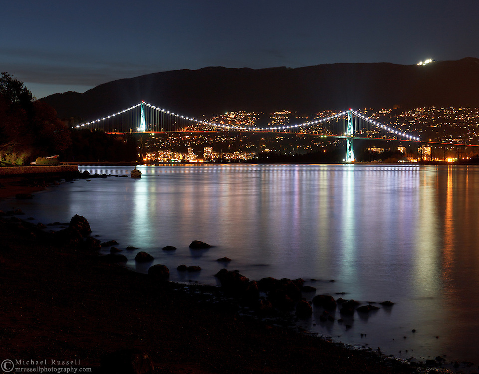 The lights of the Lions Gate Bridge reflect in Burrard Inlet at Stanley Park - Vancouver, British Columbia, Canada
