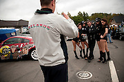 A fan of drifting racing takes a picture of young women advertising an energy drink called Burn at a competition at the Lagoisk sports complex on Sept. 26, 2009. Drifting, a racing competition popular in Ukraine, Russia, Belarus, Lithuania and Latvia, pits two street-legal cars against each other on a figure-eight track with one trying to force the other into spinning out as the two slide around the course.