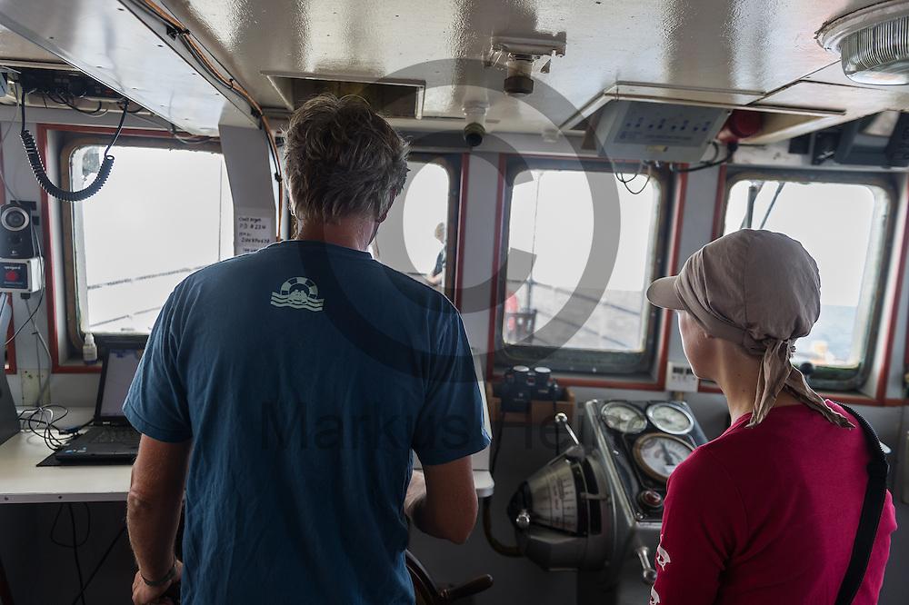 Der Bordarzt Frank Doerner steuert am 21.09.2016 unter Aufsicht der erste Offizierin Charlotte Peters das Fluechtlingsrettungsboot Sea-Watch 2 weg von der Kueste von Lampedusa, Italien. Foto: Markus Heine / heineimaging<br /> <br /> ------------------------------<br /> <br /> Veroeffentlichung nur mit Fotografennennung, sowie gegen Honorar und Belegexemplar.<br /> <br /> Publication only with photographers nomination and against payment and specimen copy.<br /> <br /> Bankverbindung:<br /> IBAN: DE65660908000004437497<br /> BIC CODE: GENODE61BBB<br /> Badische Beamten Bank Karlsruhe<br /> <br /> USt-IdNr: DE291853306<br /> <br /> Please note:<br /> All rights reserved! Don't publish without copyright!<br /> <br /> Stand: 09.2016<br /> <br /> ------------------------------