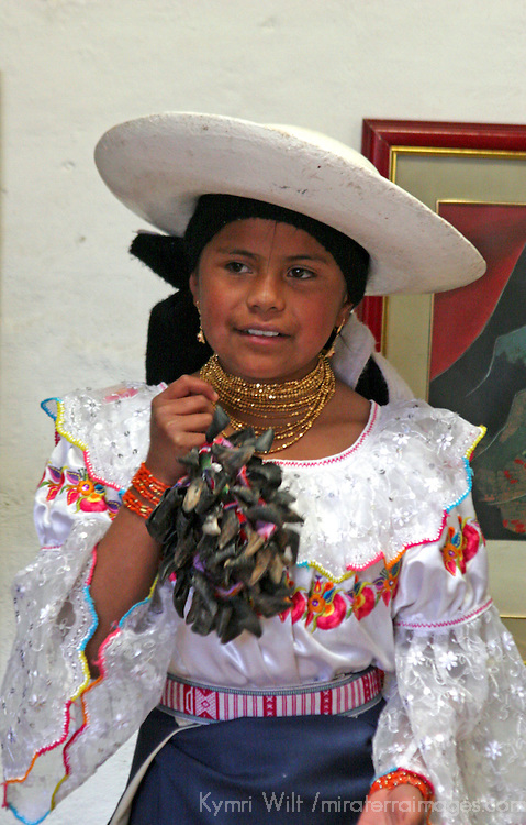 South America, Ecuador, Peguche. A youg girl in a family of musicians demonstrates percussion.