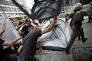 Protesters chase away a riot police officer after clashes in the side streets of Athens..  Whilst the MPs in parliament prepare to debate new austerity measures required for the EU and IMF bail-out package.  Athens, Greece turned into a war zone with many arrests and tear gas thrown by the police.  Image © Angelos Giotopoulos/Falcon Photo Agency