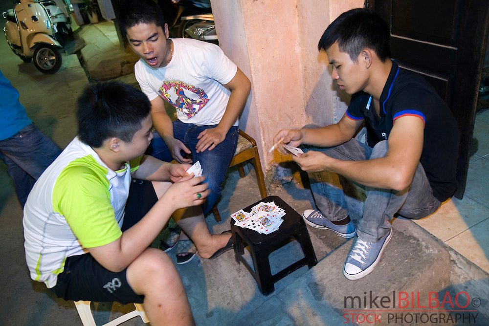 young men playing cards in the street.<br /> Hanoi, Vietnam.