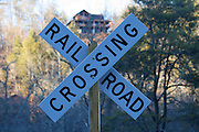 A rail road crossing sign in a field in the back woods of the North Georgia Mountains with a house on the hilltop in the background.