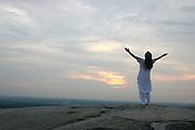 Barefoot, Spiritual Woman raises her arms to greet the dawn atop the giant, granite rock that is Stone Mountain, Georgia.