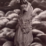 Woman on top of the world with phases of the moon (series of 4) Woman standing on the globe with the moon over her shoulder, circa 1900.