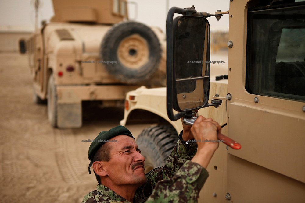 Afghan National Army member fixes a side mirror of a army humvee vehicles at Camp Pamir carpark near Kunduz.