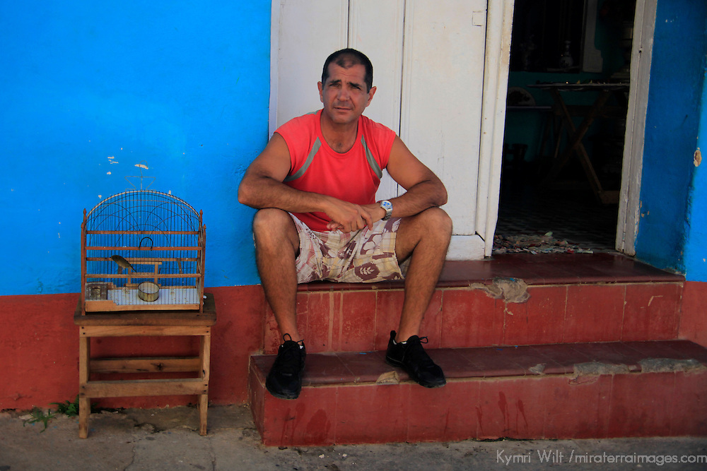 Central America, Cuba, Trinidad. Cuban man on steps with caged bird.