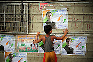A boy hags posters supporting India's Congress party near a polling station during the second phase of voting in parliamentary elections April 23, 2009 in the Muslim dominated town of Mukalmua in the stare of Assam, India.  Congress party leaders Rahul Gandhi and Kamal Nath, the commerce minister, and key government allies face Indian voters today in the second round of polling in a five-stage general election.