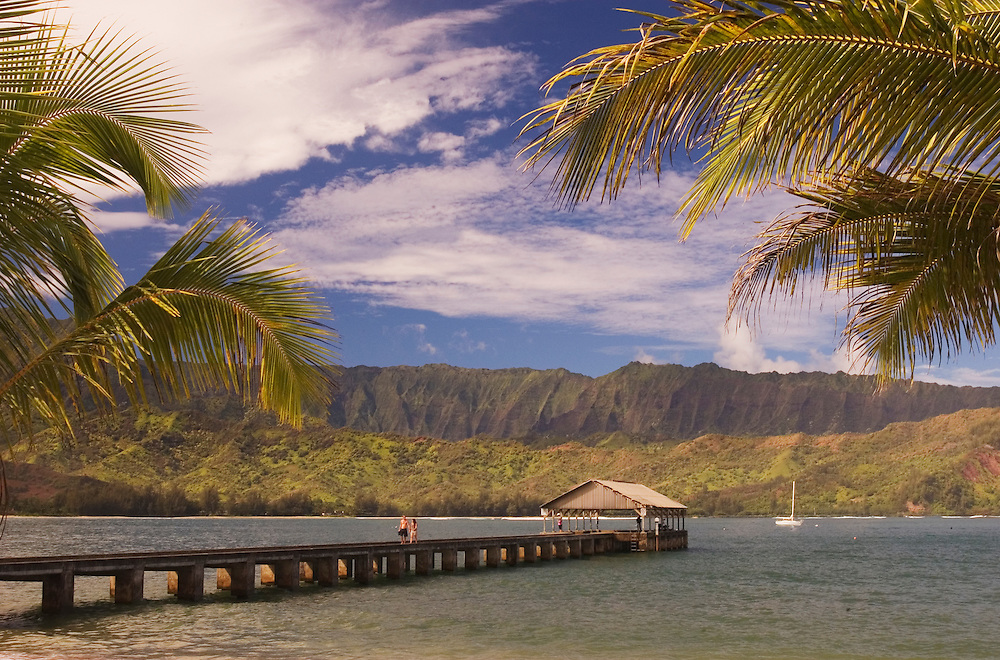 Hanalei Bay, Kauai, Hawaii, with couple on pier and sailboat anchored in bay.