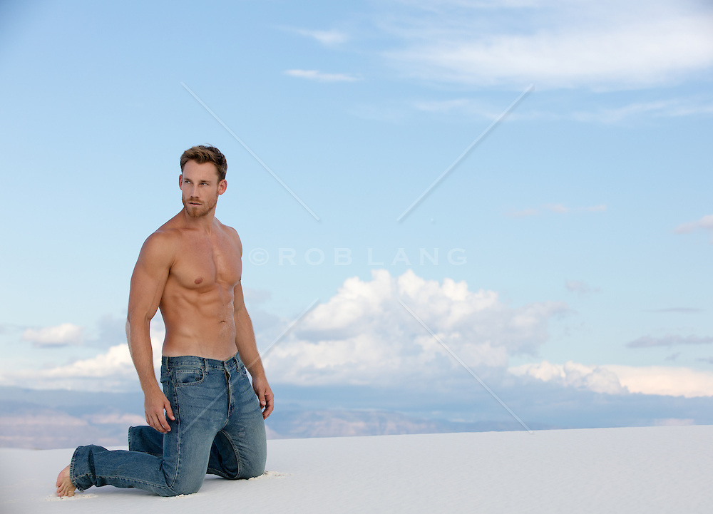 shirtless hunky man kneeling  on a sand dune in White Sands, NM