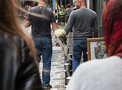 """Compton Street, Soho, London, June 13th 2016. A pair of white roses, a solemn memorial to the 50 people killed at gay club Pulse in Orlando on 12 June, is attached to the balustrade outside The Admiral Duncan, a LGBT-friendly bar that knows too well the price of homophobia, bombed by Neo-Nazi David Copeland on 30 April 1999, killing three people and wounding 70. The message on the card reads, """"Compton Street, Soho, London, June 13th 2016. A pair of white roses, a solemn memorial to the 50 people killed at gay club Pulse in Orlando on 12 June, is attached to the balustrade outside The Admiral Duncan, a LGBT-friendly bar that knows too well the price of homophobia, bombed by Neo-Nazi David Copeland on 30 April 1999, killing three people and wounding 70. The message on the card reads, """"To Orlando, LOVE IS LOVE! Soho stands with you."""" and is signed """"James and Talia"""". PICTURED: Two men walk hand in had along Old Compton Street."""