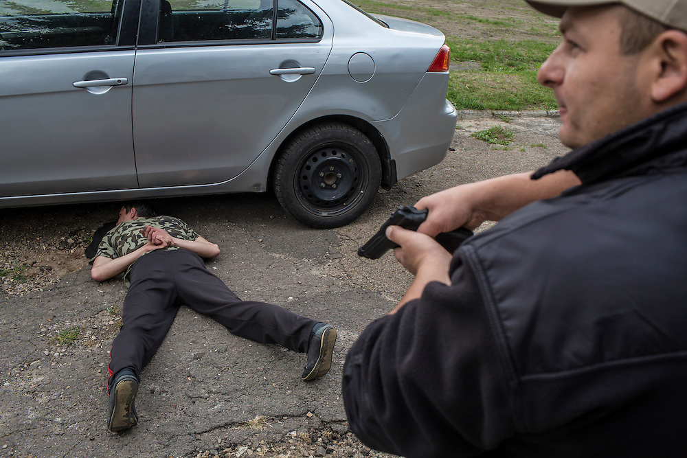 LVIV, UKRAINE - OCTOBER 5, 2015: Instructor Yurii Shevchyk, right, teaches recruits how to apprehend a suspect during a traffic stop during tactical training for new patrol police officers in Lviv, Ukraine. In an effort to reform the notoriously corrupt Ukrainian police force, an entirely new force has been established in several cities, including Kiev and Lviv, with a primary focus on patrolling the streets. CREDIT: Brendan Hoffman for The New York Times